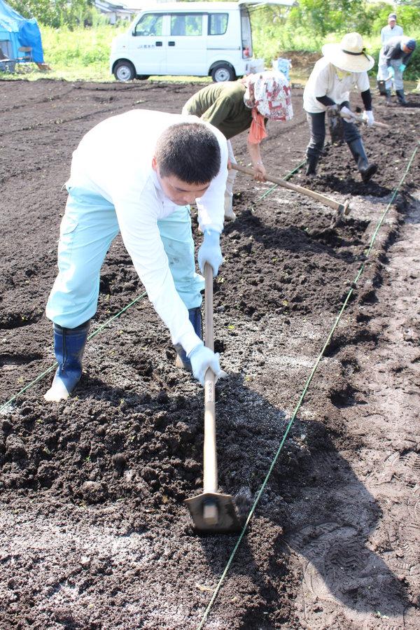 慣れない手つきで、土に肥料を混ぜる研修生ら
