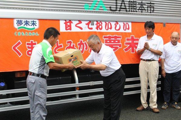 トラックの運転手に「豊福早生」を手渡す中川部会長