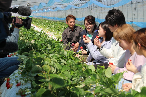 テレビカメラの前で地元タレントや大学生に「ゆうべに」の魅力を説明する村上さん(中央)