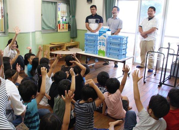 生産者の「牛乳が好きな人〜?」の質問に一斉に手を上げる園児ら