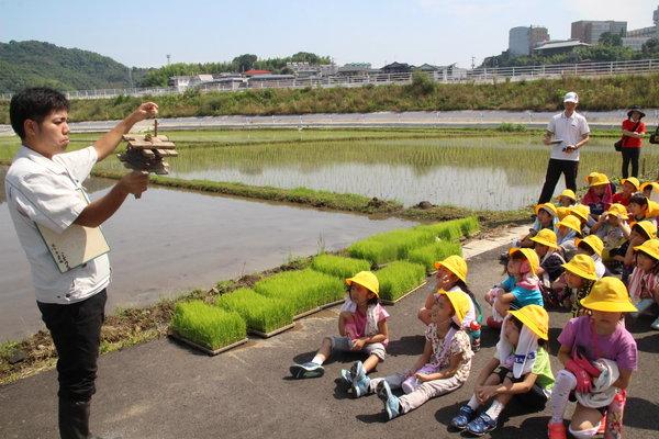 小学生に田植えの説明をする営農指導員(左)(6月22日、市内西区の圃場にて)