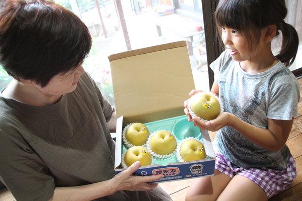 中川さん(右)から梨「豊水」を受け取り、笑顔の葵ちゃん